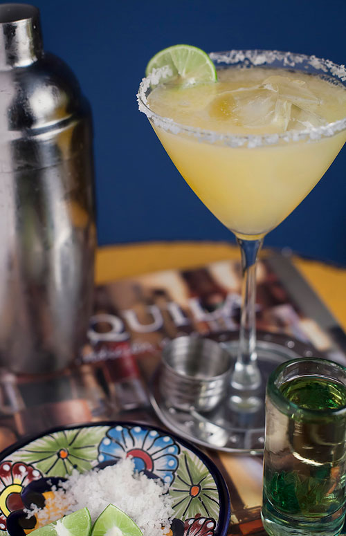 Gold Margarita next to a cocktail shaker and a tequila shot